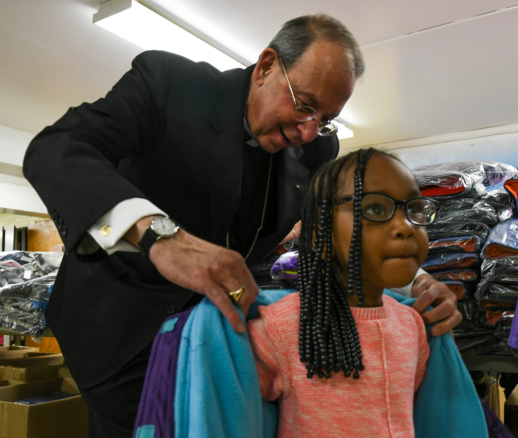 Archbishop William E. Lori helps a girl try on a new coat